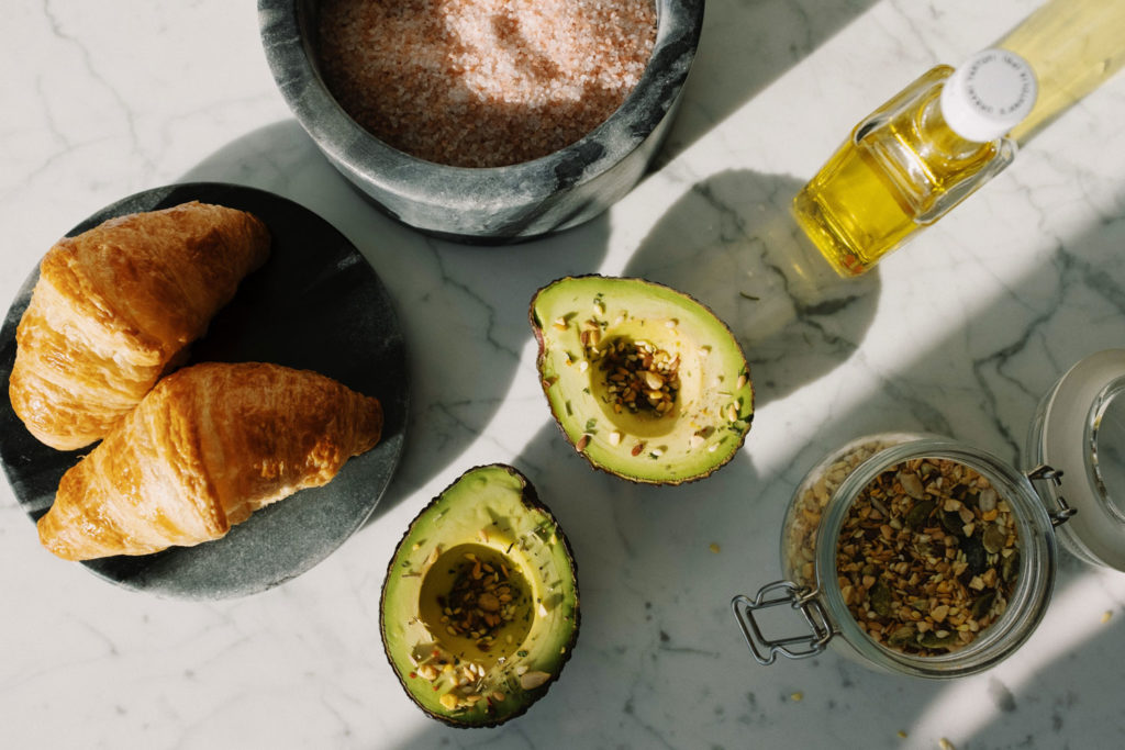 Table setting with fatty food, avocado, croissant, olive oil