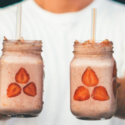 Person holding two strawberry protein shakes